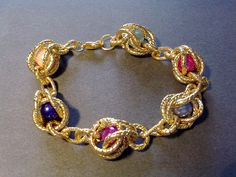 Bracciale composto da anelli in alluminio dorato e perle di vari colori, montato con componenti in metallo color oro. Realizzazione artigianale.