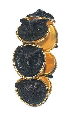 Pinchbeck bracelet circa 1880, set with a row of carved bog oak owls in rope-twist mounts.