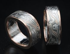 Custom designed pair of mokume wedding bands in custom billet of palladium 500/sterling silver with ribbon of 14K red gold.