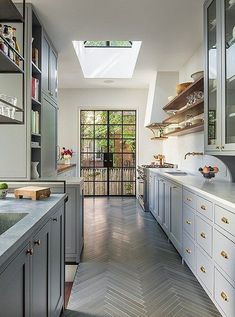 Love the perfect gray color of these kitchen cabinets, paired with the brass hardware, carrara marble counters and gray herringbone parquet floors.