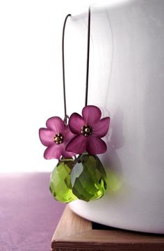 Artist Statement:  Richly-hued, matte acrylic flower blossoms in deep velvety  violet are  matched with contrasting large olivine green faceted glass teardrops.