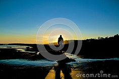 Man standing at sunset on beach creates silhouette