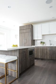 A gray veneer kitchen island topped with a white quartz countertop seats two white tufted and gold bar stools, Nuevo Chi Bar Stools, and is fitted with a stainless steel microwave.