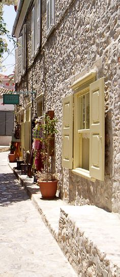 Shutters can be found on homes and businesses across the globe. Where do you think these shutters are located? (Hint: take a peak at the stone road.)