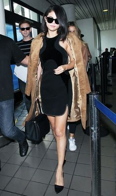 Selena Gomez wears a black cutout top dress, suede trench coat, and pointed-toe heels