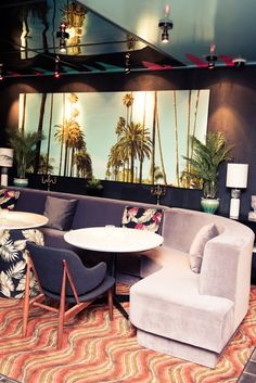 A Guide to L.A.'s West Hollywood Neighborhood: Doheny Room, Light Grey Velvet Seat with Navy Blue Chair and Floral Pillows, Palm Tree Photograph | coveteur.com