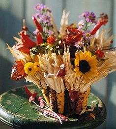 Attach 12 to 13 ears of ornamental corn (including husks) to a 6-inch terra-cotta pot, using hot glue. Fill with asters, peppers, safflowers, gourds, pompons, sunflowers, rosehips and maple leaves.