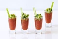 gazpacho shot glasses topped with a dressing of avocado and cucumber