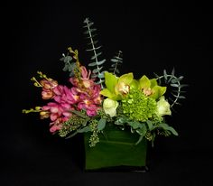 This is a cube vase floral arrangement that features mokara orchids, hydrangea, cymbidium orchids and roses in a pink, green and white color scheme. See our entire selection at www.starflor.com.  To purchase any of our floral selections, as gifts or décor, please call us at 800.520.8999 or visit our e-commerce portal at www.Starbrightnyc.com. This composition of flowers is generally available for same day delivery in New York City (NYC).   SQ295
