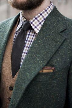 Shop this look on Lookastic: https://lookastic.com/men/looks/blazer-waistcoat-long-sleeve-shirt-tie-pocket-square/13475 — Violet Gingham Long Sleeve Shirt — Dark Brown Wool Tie — Brown Wool Waistcoat — Dark Green Wool Blazer — Brown Pocket Square