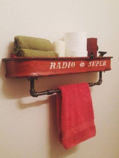 Radio Flyer Radio Super wagon cut in half and mounted to the wall as a shelf with black iron pipe as a towel holder underneath.