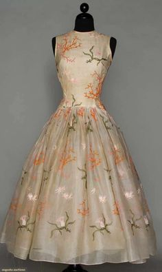 NORELL EMBROIDERED WHITE PARTY DRESS, c. 1954. Cotton organdy w/ orange coral, pink sea anemone & green frond embroidery, sleeveless, fitted & drop waist bodice, knife pleated voluminous bell skirt; 4 attached petticoats.