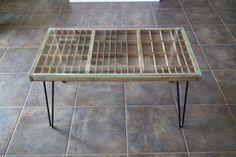 Typesetter tray table with hairpin legs and glass top.