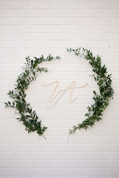 Dark green olive branches draw the eye to gold initials for a bold effect against a white brick wall.Related: Creative Ways To Use Your Monogram