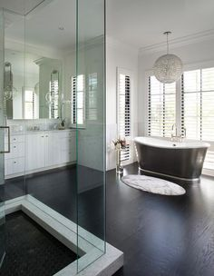 White and black contemporary bathroom features a glam chandelier hung over a black cast iron bathtub placed on an ebony oak wood floor in front of windows covered in white plantation shutters, while an oval marble bathmat sits in front of the tub. Wood Floor Bathroom, Bathroom Windows, Bathtub Tile, Bathroom Mirrors, Master Bathroom, Bathroom Lighting, Dark Wood Bedroom, Wood Bedroom Sets, Black Wood Floors