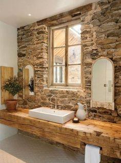 Badkamer met stenen muur en houten tafel.