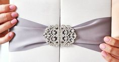 Wedding Invitation| MIRANDA This handcrafted silk gatefold is the ultimate in #luxury. The detailed #crystal scroll clasp and 3 #satin #ribbon is the prime jewel of this white silk folio.  #EngagingPapers #bridetobe