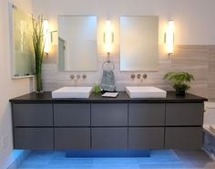 Dual vessel sinks and a pedestal vanity help create a modern approach in this bathroom. Do you like the light fixtures? Design by http://www.changeyourbathroom.com/