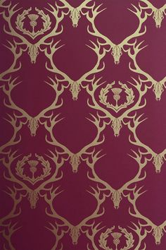 Deer Damask Wallpaper Deep raspberry red wallpaper with gold stag head and antlers with thistle design
