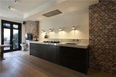 Mooie contrast tussen strakke keuken en stenen muur!