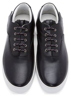 "Black Leather Fringed Platform Sneakers by Krisvanassche. Low-top pebbled leather sneakers in black. Round toe. Multicolor laces in oxford-style lace-up closure. Fringe detail at tongue. Velcroed ""wing"" detail at side collar. Platform sole in white. Tonal stitching. Approx. 1.5"" platform. Upper & lining: leather. Sole: rubber. Made in Italy. http://www.zocko.com/z/JE7oo"