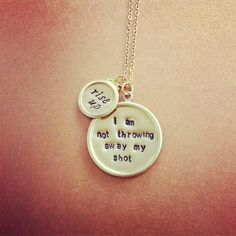 """My Shot Necklace Inspired By Hamilton Broadway Musical  Stamped on gold tone tray pendants are the quotes """"rise up"""" and """"I am not throwing away my shot""""- a nod to Alexander Hamilton from the musical named for him."""