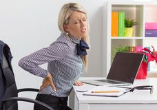 Woman having back pain while sitting at desk in office Stock Photo