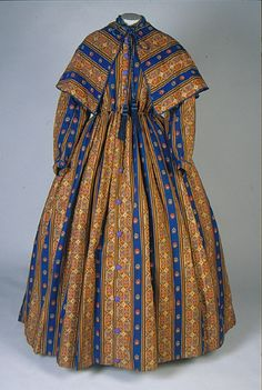 Printed wool challis dress with matching cape. Print consists of alternating royal blue and gold/brown vertical stripes. 1863-65; American Textile History Museum.