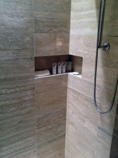 Shower shelf or niche wraps around the corner. Great idea!   Natural stone shower. Not the best image quality but great idea