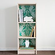1. Clear out your bookshelf and lay it flat on its back. 2. Measure the space between the shelves and cut your wallpaper to size using a utility knife and metal ruler as your guide.  3. Apply an even layer of spray adhesive to the back side of your wallpaper and press firmly to the back of the shelf.