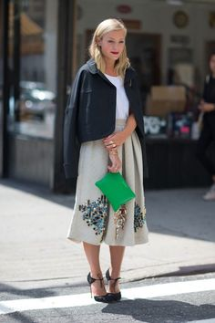 inspiração street style look saia mídi com jaqueta preta, top branco, saia mídi bege bordada, scaprin preto, clutch verde, mix de anéis