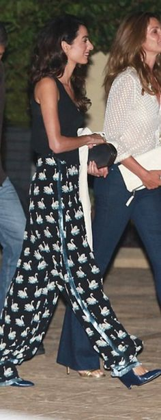 Who made  Amal Clooney's black clutch handbag and swan print pants
