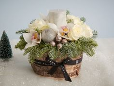 Jane Packer - Chalet, £70.00 (http://www.janepackerdelivered.com/chalet/) Description This table centre design is full of crisp white roses and cymbidium orchids with glistening baubles and waxed apples. The perfect centre piece for your festive feast.
