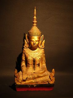 Laos wooden seated king Buddha, or sometimes known as 'Crowned Buddha', wearing a diadem-crown and jeweled ornaments of a king instead of ordinary monk's robe. King buddha represents the Buddha's role as a universal sovereign.