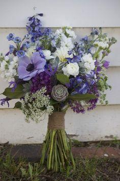 Wildflower rustic bouquet of blue delphinium, white Ranunculus, succulents, purple Anemone, white Stock, Queen Anne's Lace, purple Allium. Handle wrapped in twine. - Design by J. Morris Flowers