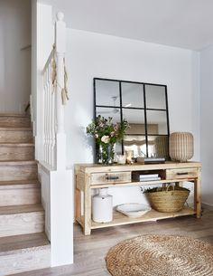 Recibidor con escalera y aparador de madera, espejo, jarrones de cerámica, cestos y alfombra de fibra 00436810 O