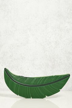 A faux leather clutch in the shape of a tropical palm leaf featuring a zippered closure with a pull tab fringe and scalloped edges.