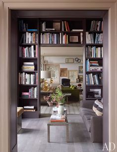 Mark Lee and Ed Filipowski at Home in Manhattan; Architectural Digest - Bookshelves by Janson Goldstein in the library frame a view of the living room. The Italian cocktail table from Mondo Cane, stained European oak flooring. Architectural Digest, Grey Bookshelves, Bookcases, Bookshelf Door, Bookshelf Ideas, Living Room Bookshelves, Bookshelf Inspiration, Painted Bookshelves, Home Libraries