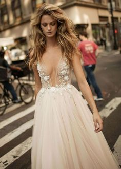 Glittering with crystal-sparked embroidery and 3D blossoms, this enchanting gown features a plunging illusion bodice and a layered tulle skirt.