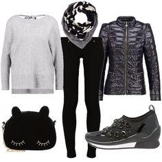 Outfit quasi total black, sdrammatizzato dalla forma divertente della borsa a tracolla e dalle sneakers impreziosite da pietre. Il piumino ha una consistenza sportiva ma una forma elegante e il pullover, all'apparenza semplice, nasconde un'intrigante scollo sulla schiena.