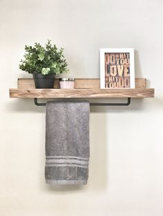 This stunning rustic wooden ledge shelf with bar saves space and is extremely functional. it Use it in the bathroom to hold candles and decor while hanging your towel or hand towel or even use it in the kitchen to hold your spices and hold your tea towels! This shelf has been hand cut, sanded smooth, stained in a dark walnut finish & coated with a wood finish to protect the wood and had a black towel rack placed on the bottom of the shelf. Dimensions: 24 x 5 x 3.5 Hanging Hardware: the...