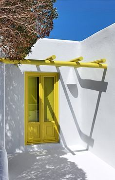 yellow and white greek architecture | Architect's House Santorini, Greece. TravelPlusStyle.com