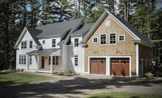 Farmhouse with natural wood carriage house garage doors. Love them against the stone.