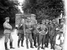 German soldiers at a border crossing between Switzerland and Germany chat with a Swiss border guard. Switzerland's neutrality during the war offered a quiet outlet to the Nazis, who took special advantage of the services of Swiss banks.