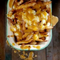 Poutine (French Fries with Gravy and Cheese Curds) by Saveur. An unabashedly savory collage of french-fried potatoes, beef gravy, and squeaky-fresh cheese curds, Poutine is perhaps the ultimate late-night snack. Poutine Recipe, Fries Recipe, Potato Dishes, Potato Recipes, Couscous, Gravy Fries, Beef Gravy, French Fries With Cheese, Canadian Food