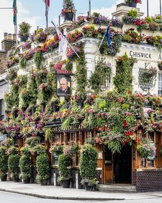 The flower covered facade of the Churchill Arms pub in Kensington, London