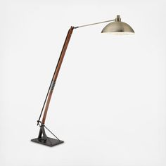 Combining a sturdy black metal base, the arm in mellow walnut, and a glowing antique brass shade, this lovely floor lamp boasts an architectural, mid-century modern look that melds seamlessly with your decor.  Maximum 150-watt or equivalent medium base bulb (not included) On/off step switch