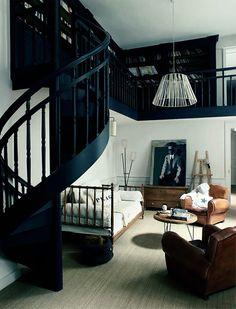 Un salon avec des escaliers noirs