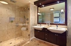 A speckled granite covers the interior of the shower, and continues on to the floor of the bathroom. The wall paper seems to blend well with the granite and both are contrasted heavily by the dark cabinets beneath the extended sinks.