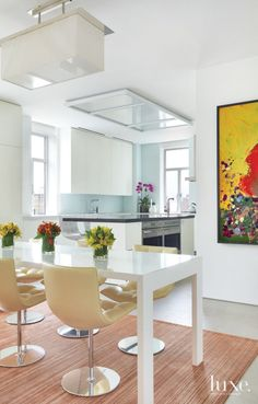 A Jasper Morrison table and leather chairs with chrome bases by Moura Starr define the eat-in area off the kitchen. The painting is by Jon Pylypchuk.